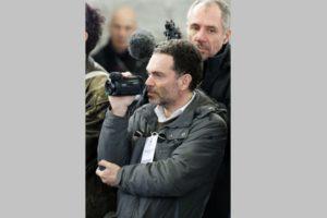 Reporter Yann Moix luistert naar de speech van Macron in Calais